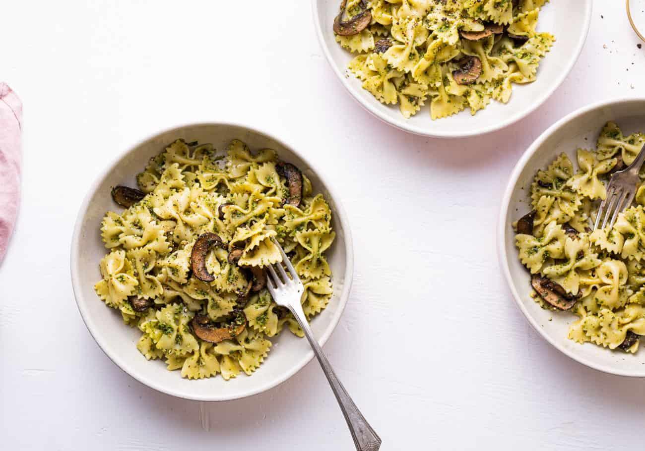 3 ceramic bowls with vegan mushroom pesto pasta on a white table