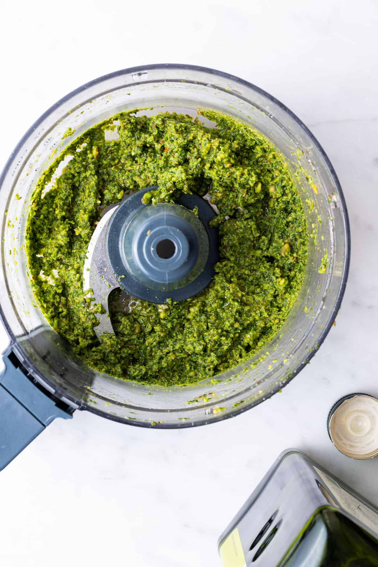 Vegan basil pesto in a food processor next to a bottle of olive oil
