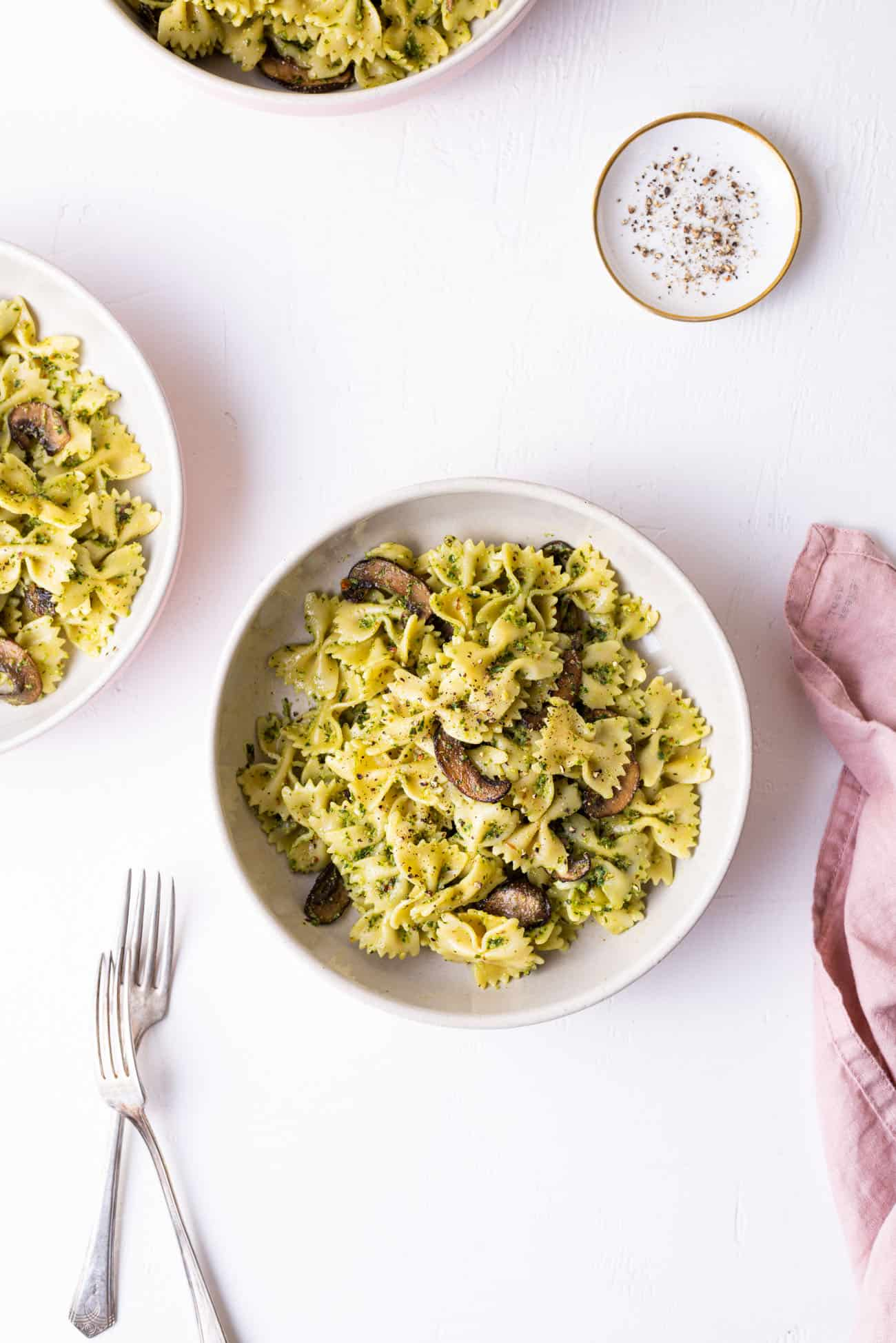 3 bowls with mushroom pesto pasta on a white table.