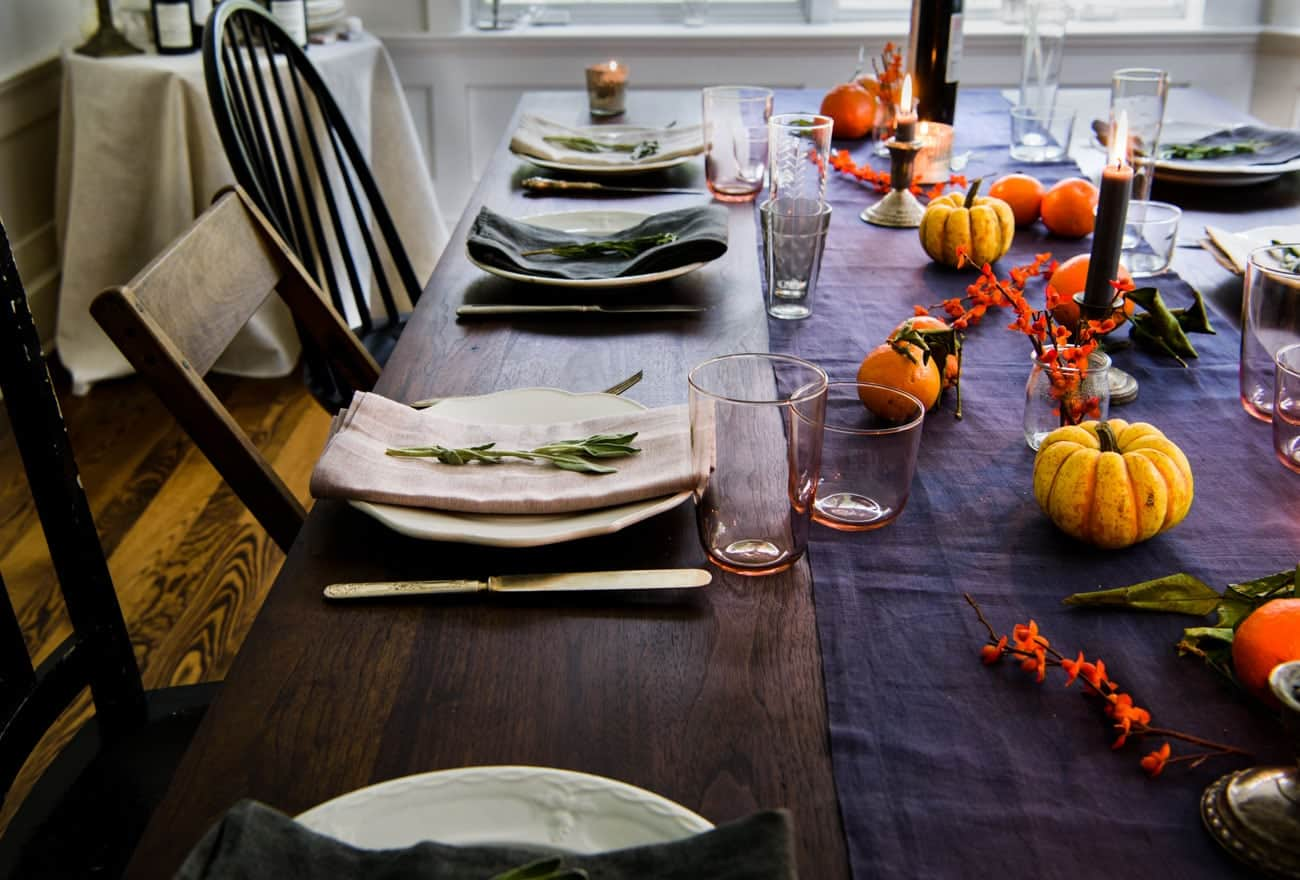 Friendsgiving tablescrape with a blue table runner and mini pumpkins - Friendsgiving Tips