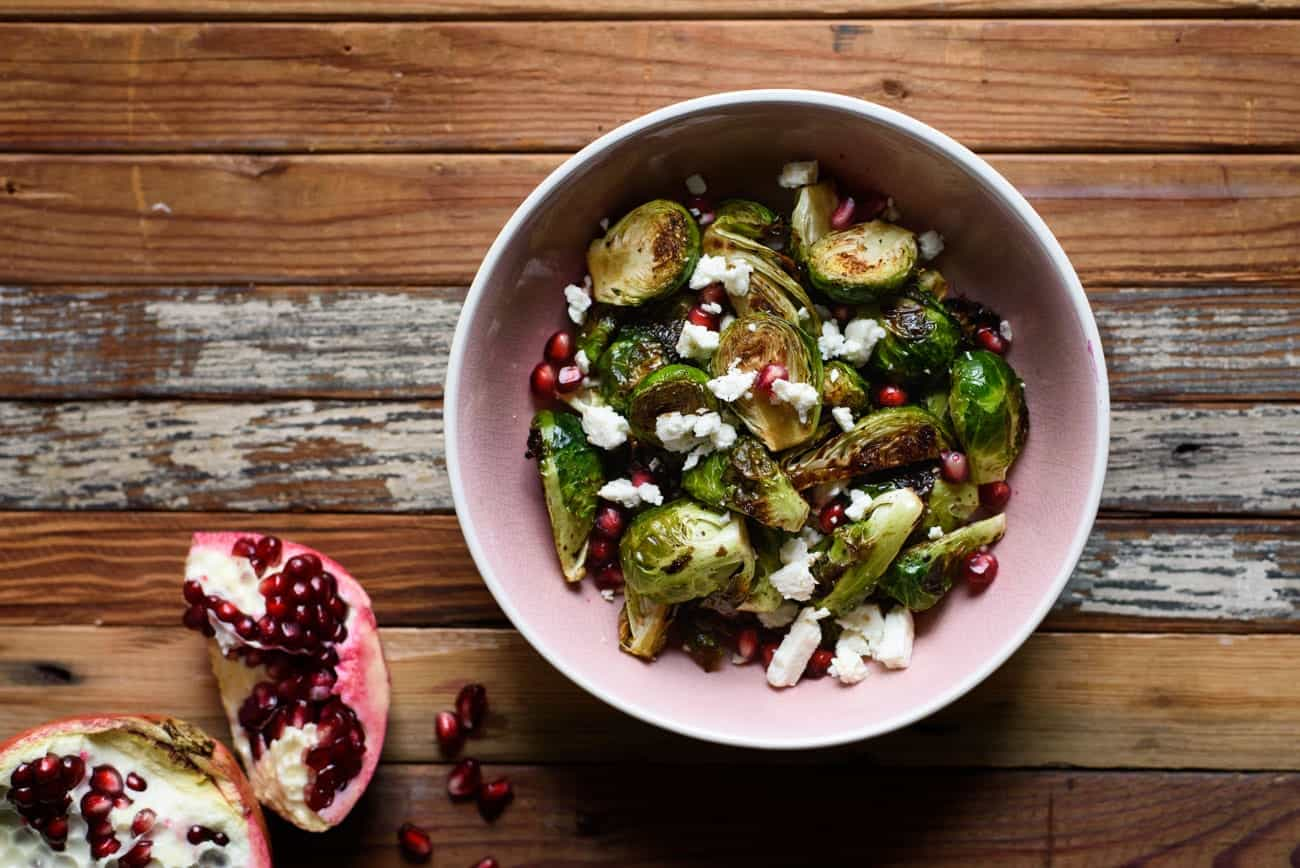 Bowl of roasted brussels sprouts with pomegranate seeds and feta cheese