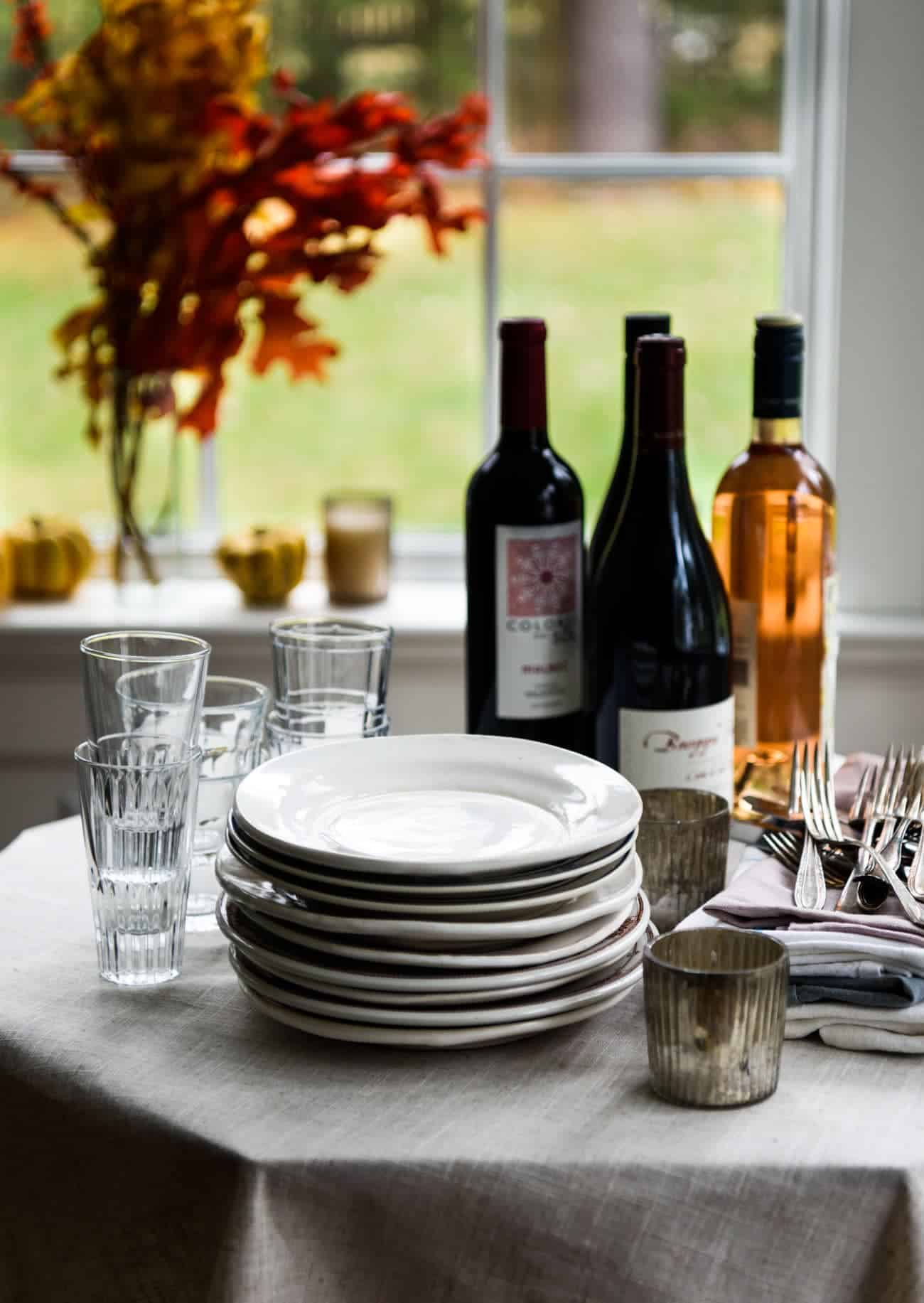 Stack of white dinner plates, bottles of wine, and glasses - Friendsgiving tips