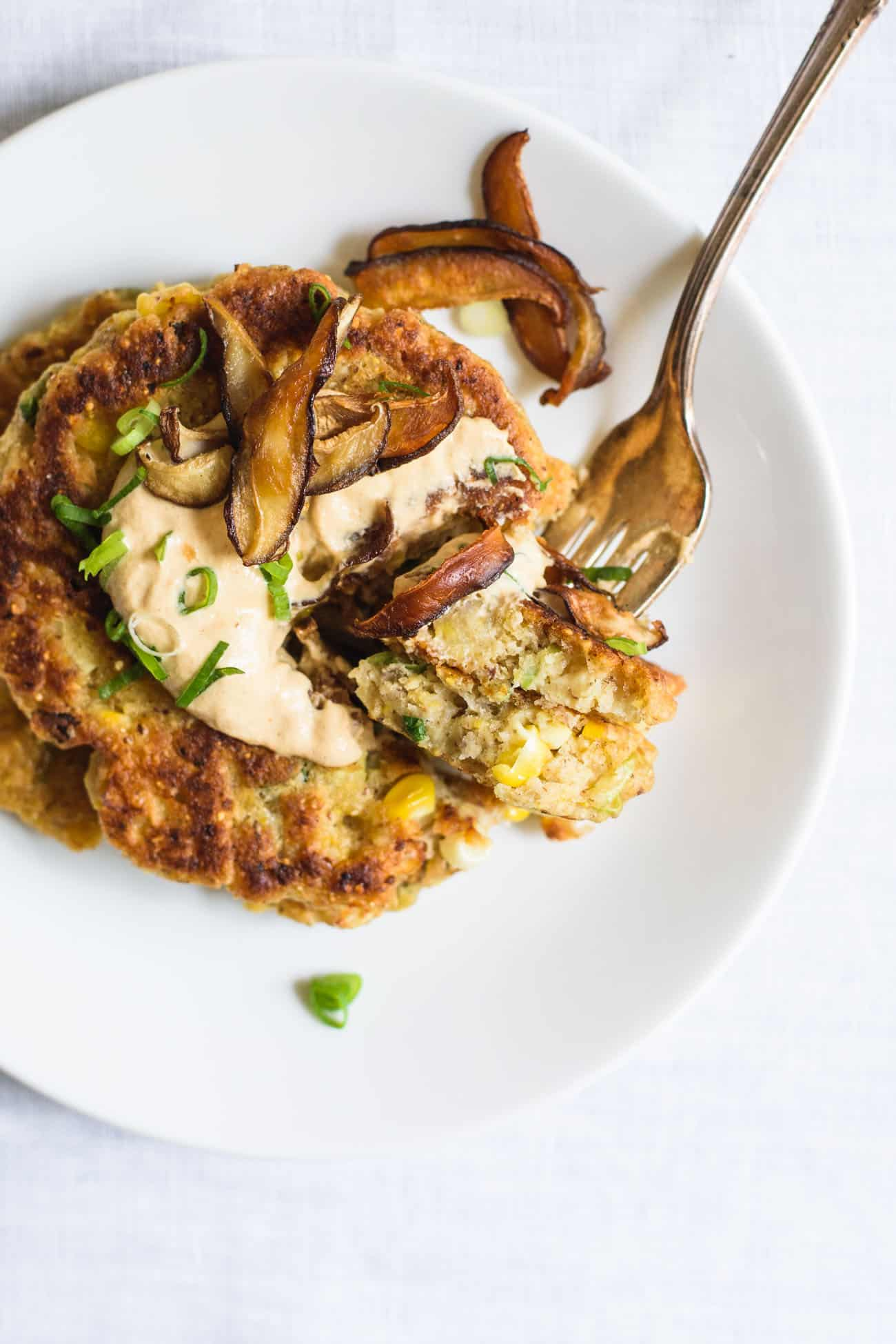 Close-up of Savory Corn Pancakes with Shiitake 'Bacon' and Chipotle Cashew Cream on a white plate with a fork