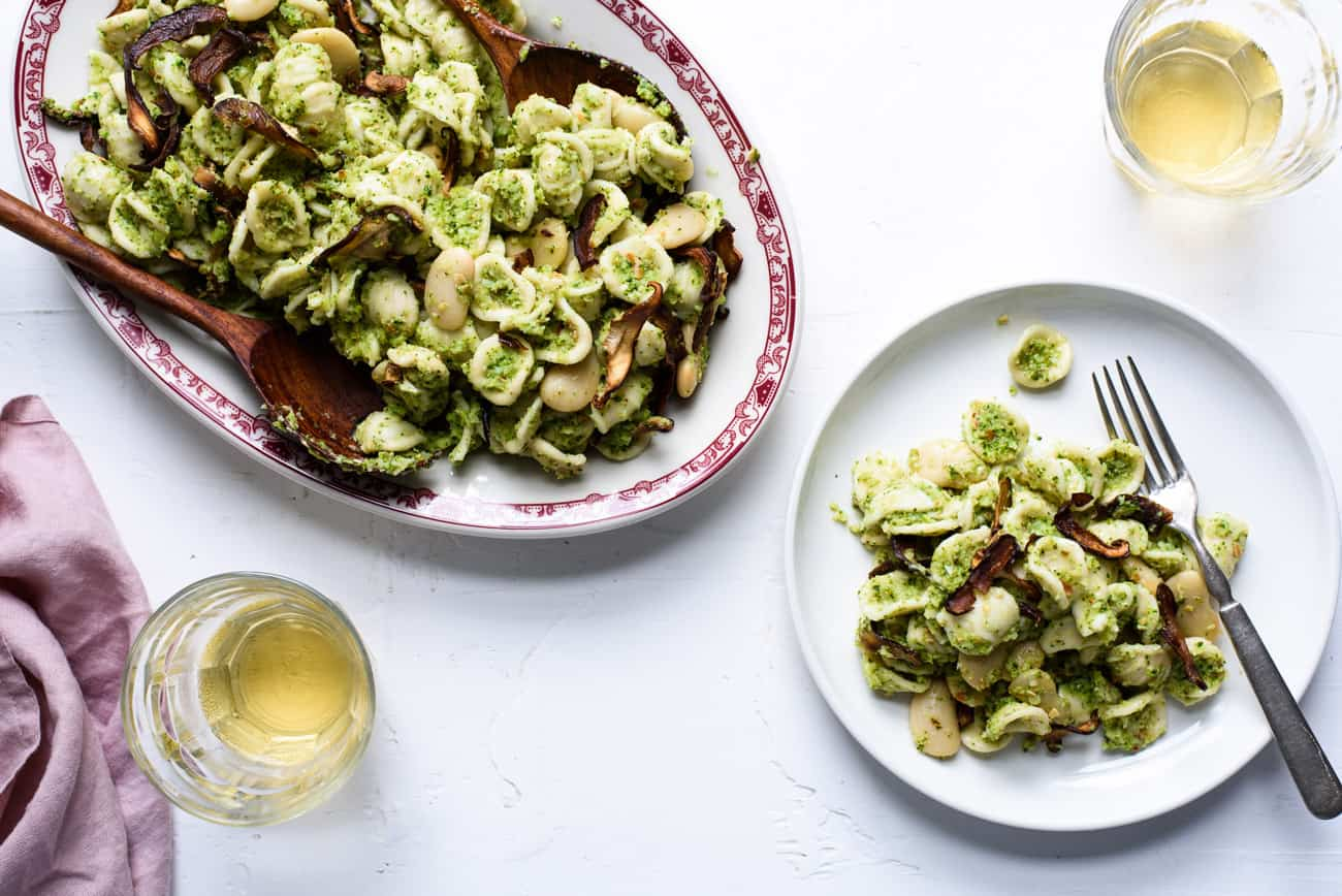 Platter of broccoli pesto pasta next to a plate and glasses of white wine