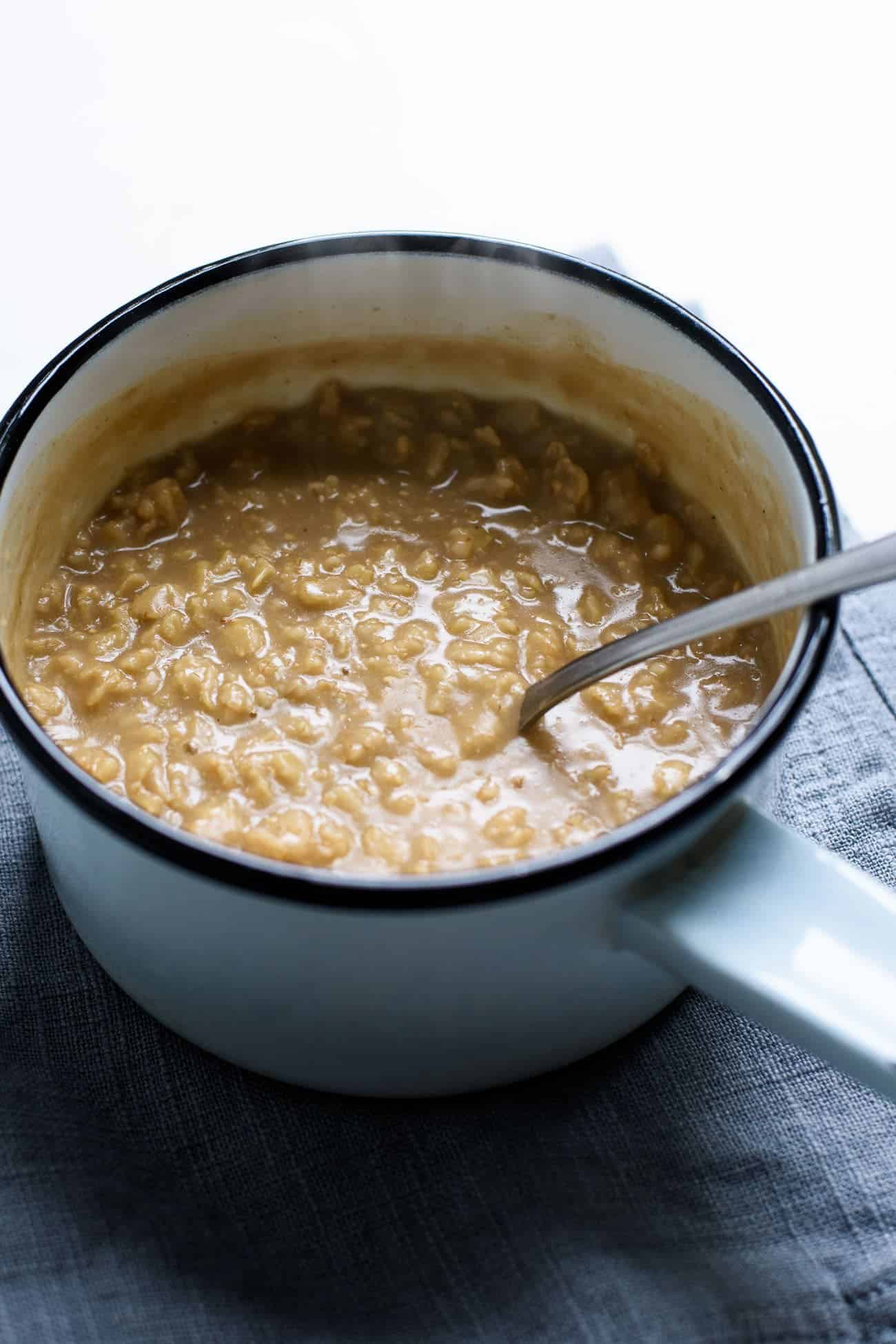 Creamy oatmeal cooked with coffee and coconut milk in a small pot