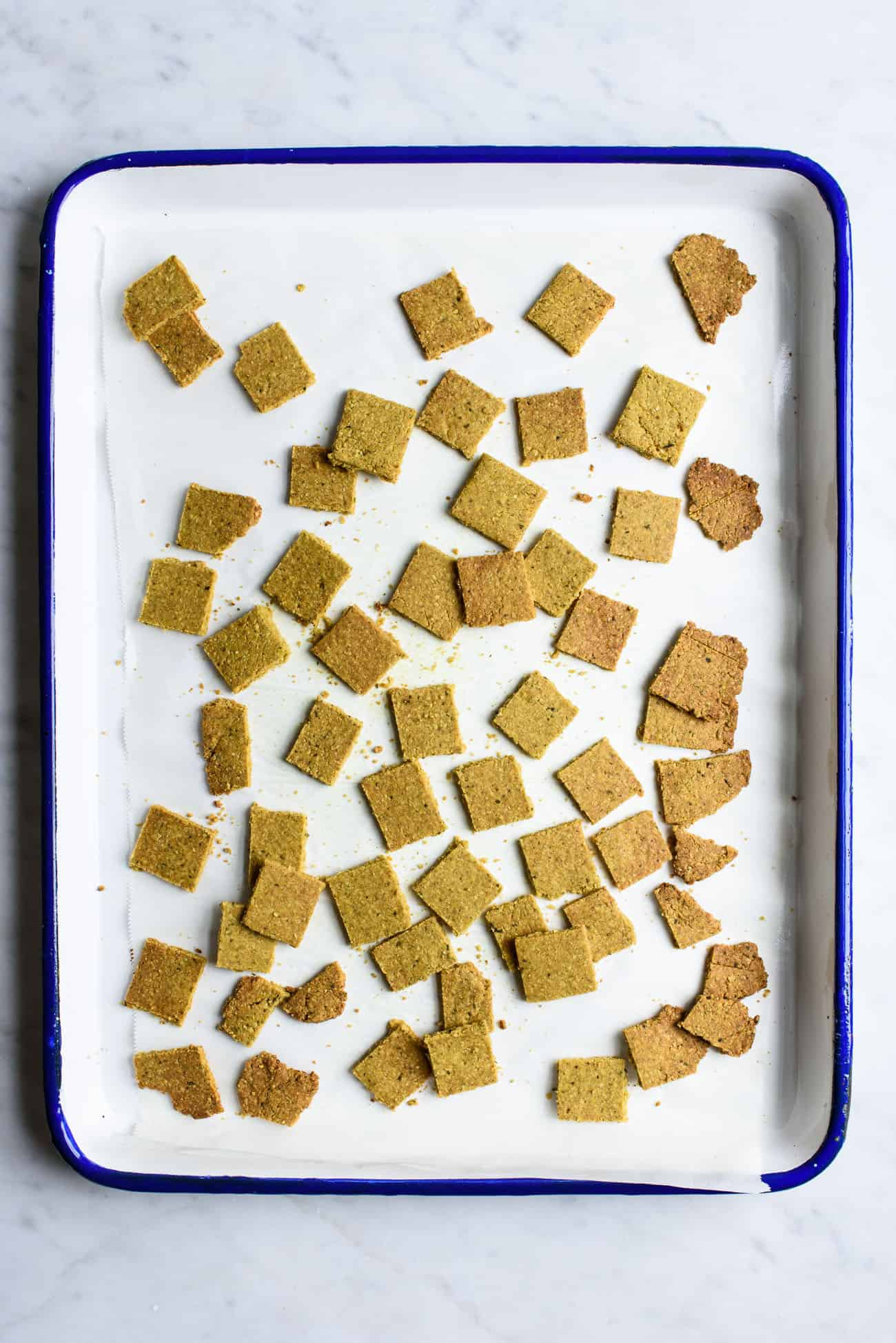 Overhead image of healthy homemade crackers on a baking sheet with parchment paper