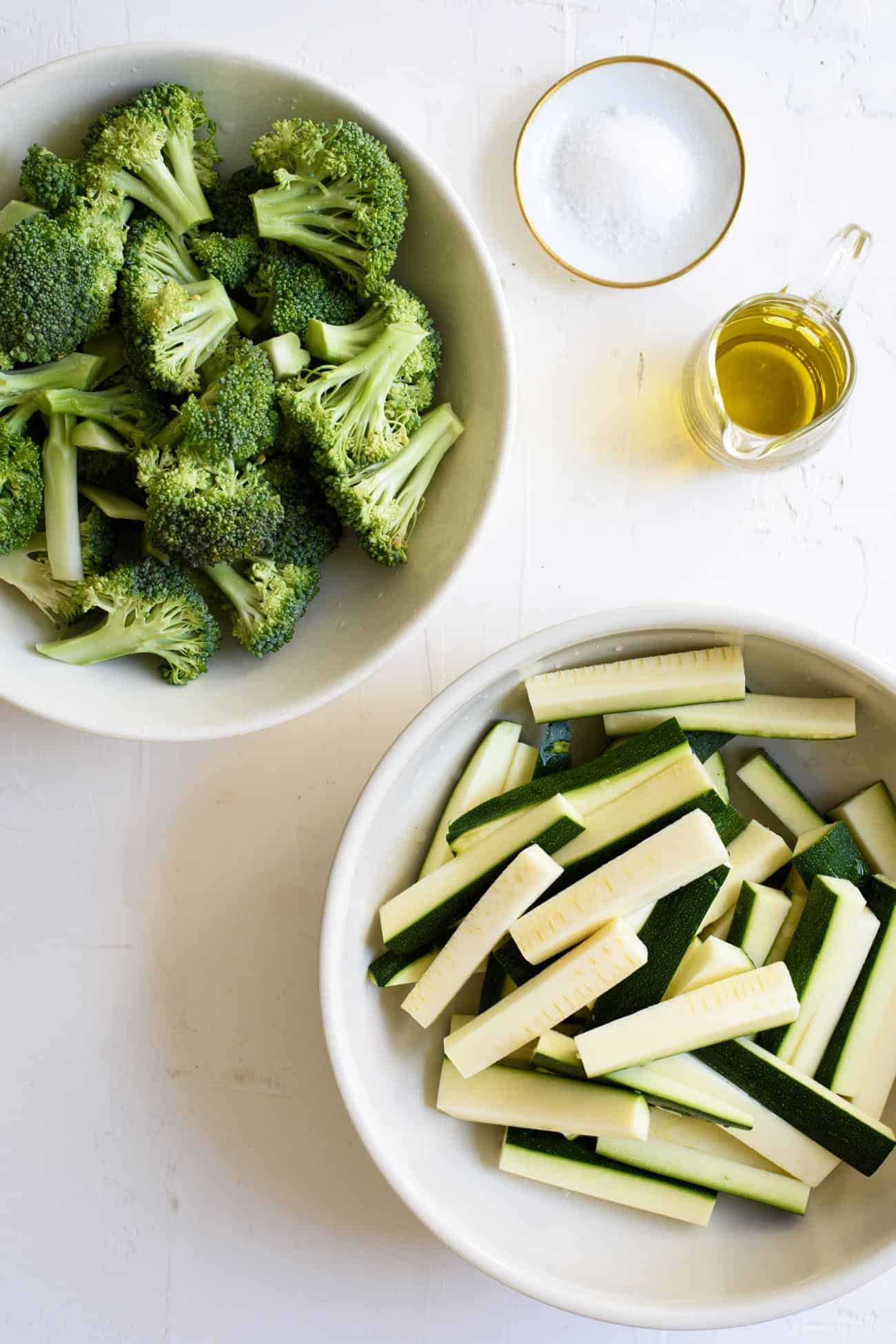 Bowls of broccoli and zucchini on a white table | A guide for How to Saute Vegetables