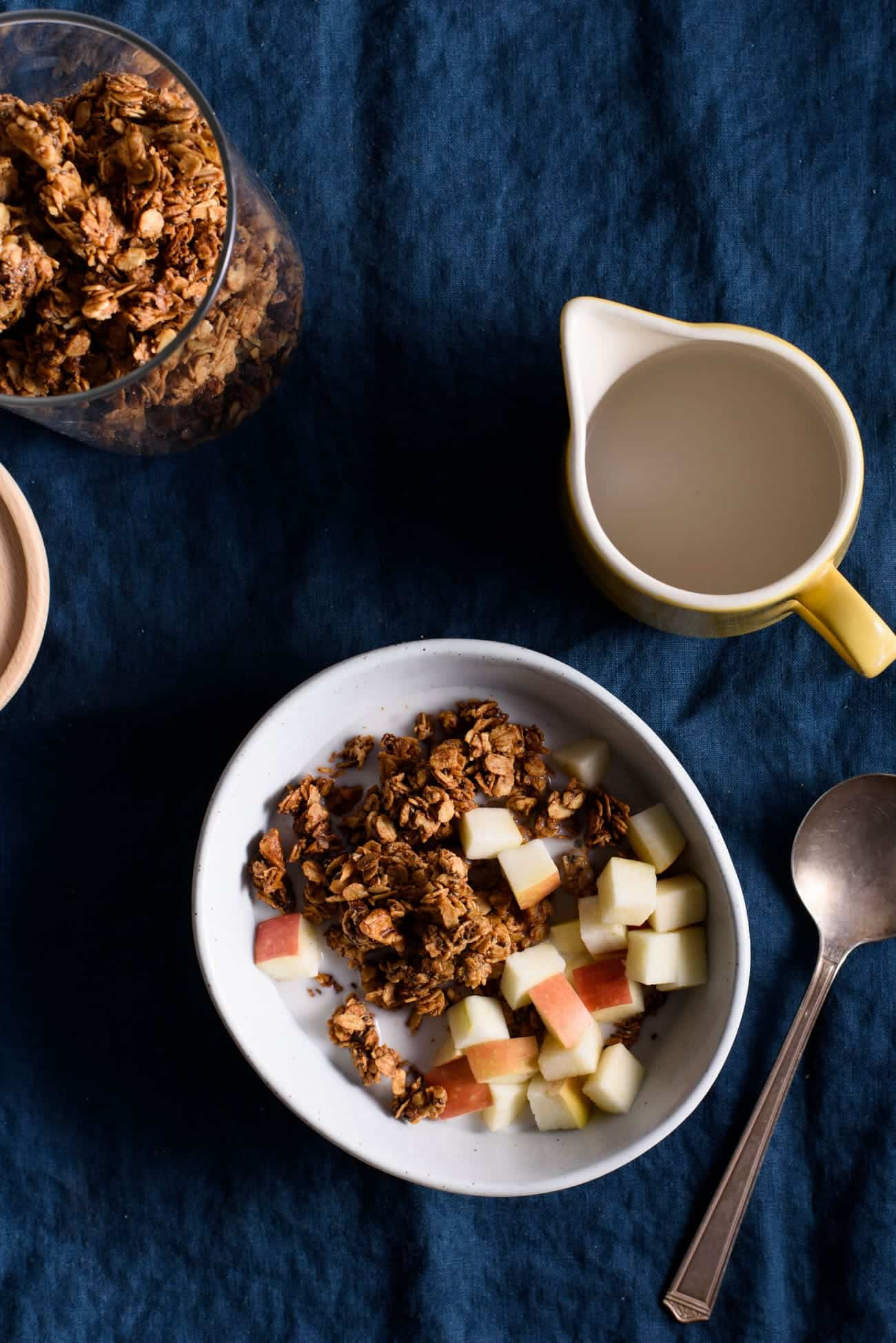 Tahini granola in a bowl on a blue tablecloth with a yellow milk pourer