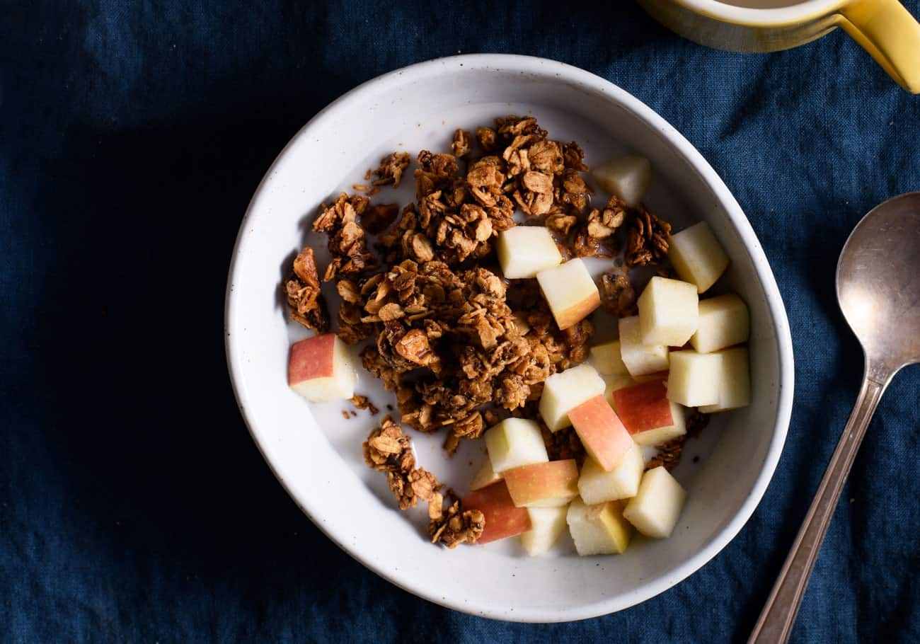 Tahini granola in a bowl on a blue tablecloth