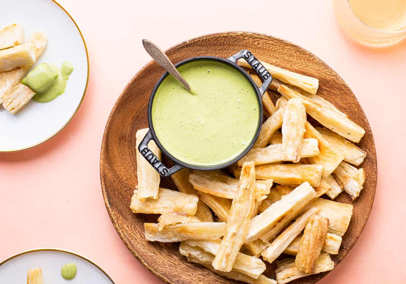 Baked Yuca Fries with a Creamy Vegan Cilantro Yogurt Dip on a small baking sheet with parchment paper