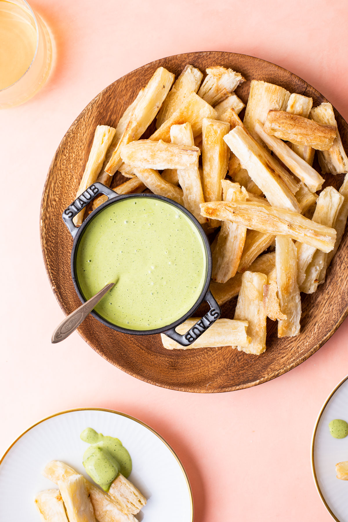 Baked yuca fries with creamy cilantro dip on a wooden plate on a pink table.
