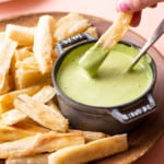 Woman's hand dipping a yuca fry into cilantro sauce.