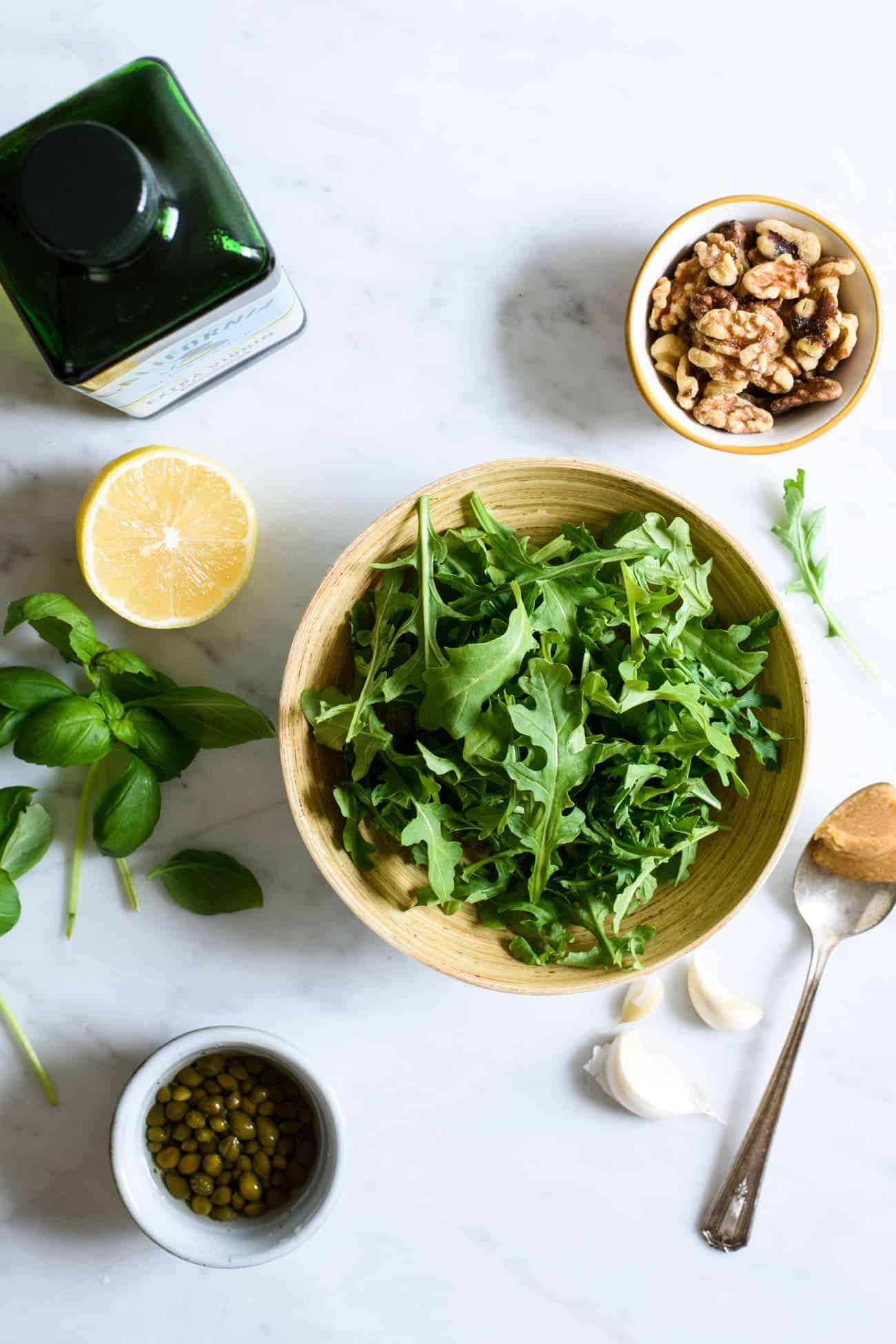 Overhead view of ingredients to make arugula-walnut pesto on a marble table