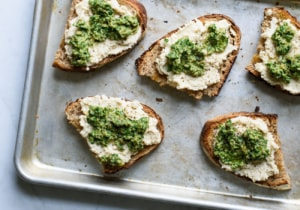 Whole wheat sourdough toasts with vegan cashew ricotta and arugula-walnut pesto on a baking sheet