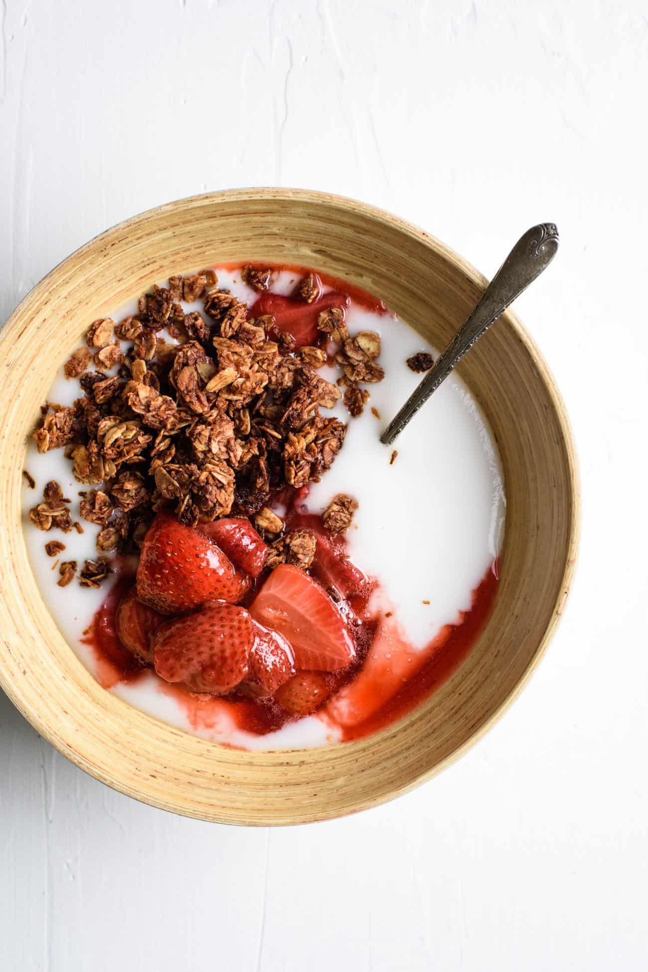 A wooden bowl of vegan yogurt with chocolate coconut granola and roasted strawberries