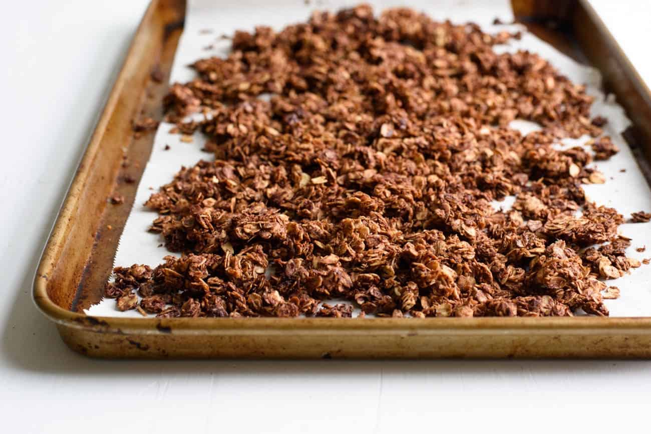 Three-quarter angle photo of chocolate coconut granola on a baking sheet