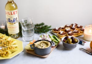 Holiday party snacks on a marble table with a bottle of Lillet Blanc