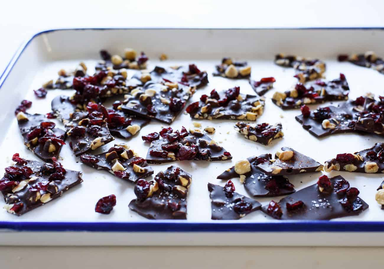 3/4-angle photo of Salted Dark Chocolate Bark with Hazelnuts, Cranberries and Cayenne Pepper on parchment paper in an enamel baking sheet