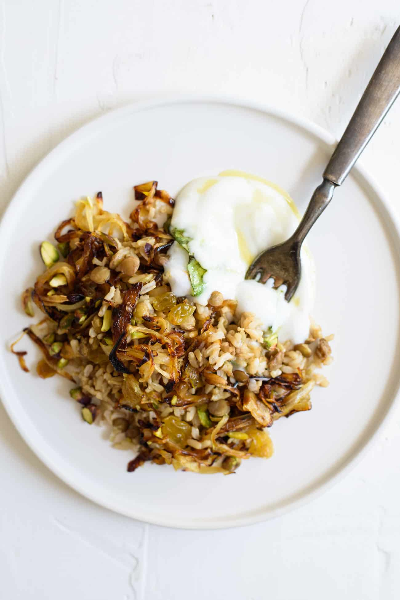 Mujadara recipe: close-up of mujadara (brown rice and lentils with fried onions) on a white plate with yogurt