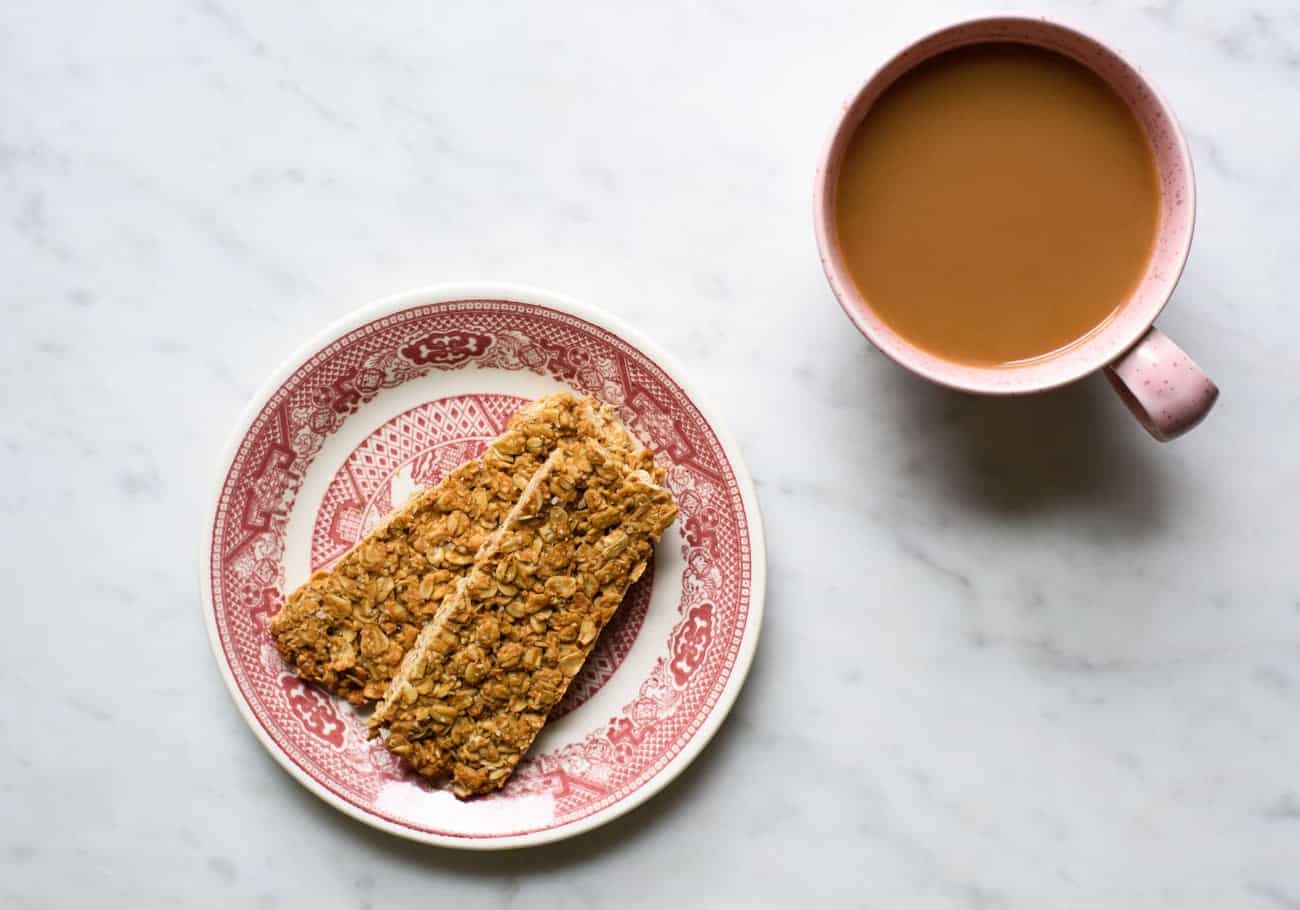 Crunchy peanut butter granola bars on a pink plate on a marble table with coffee