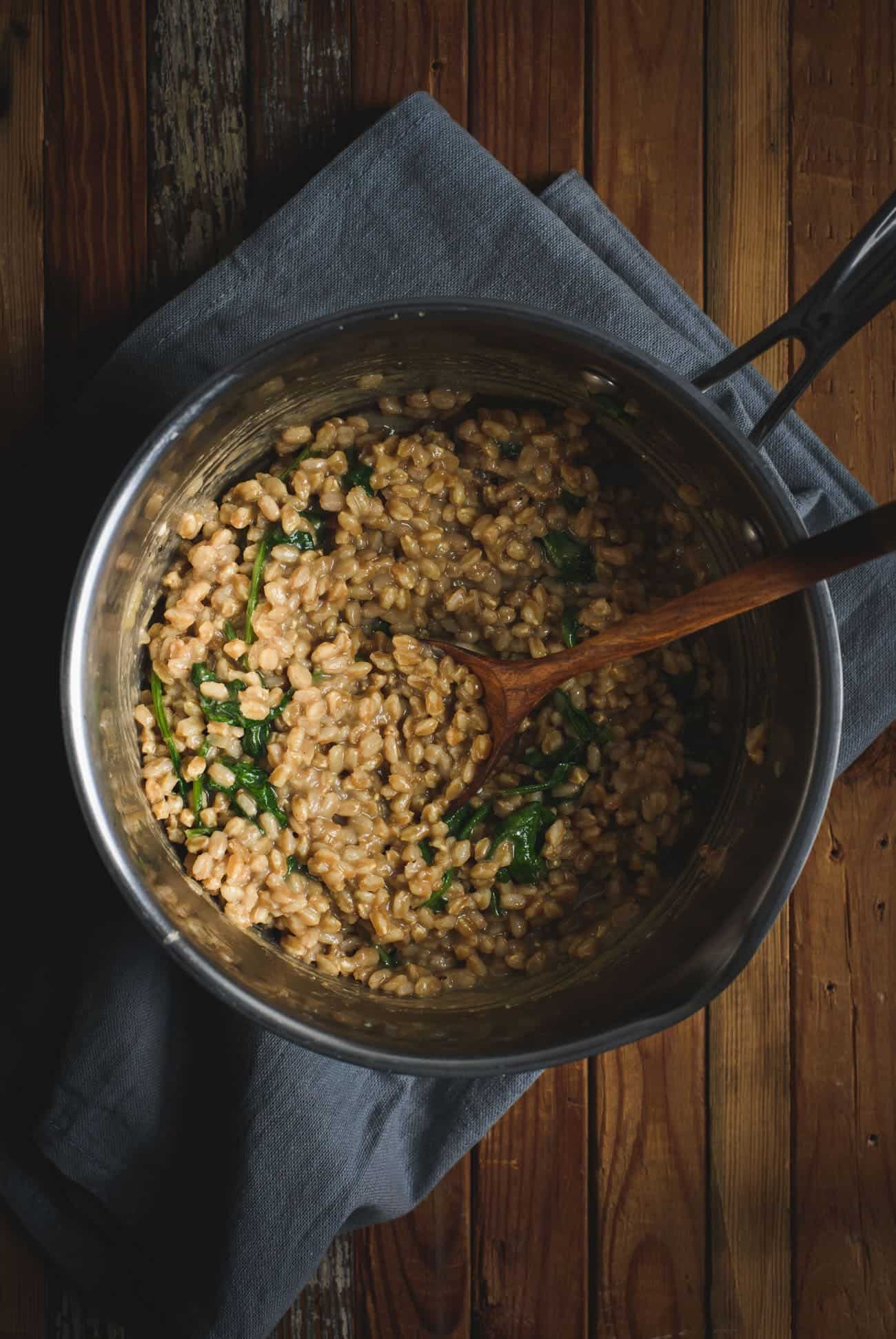 Pot of savory farro porridge with a wooden spoon