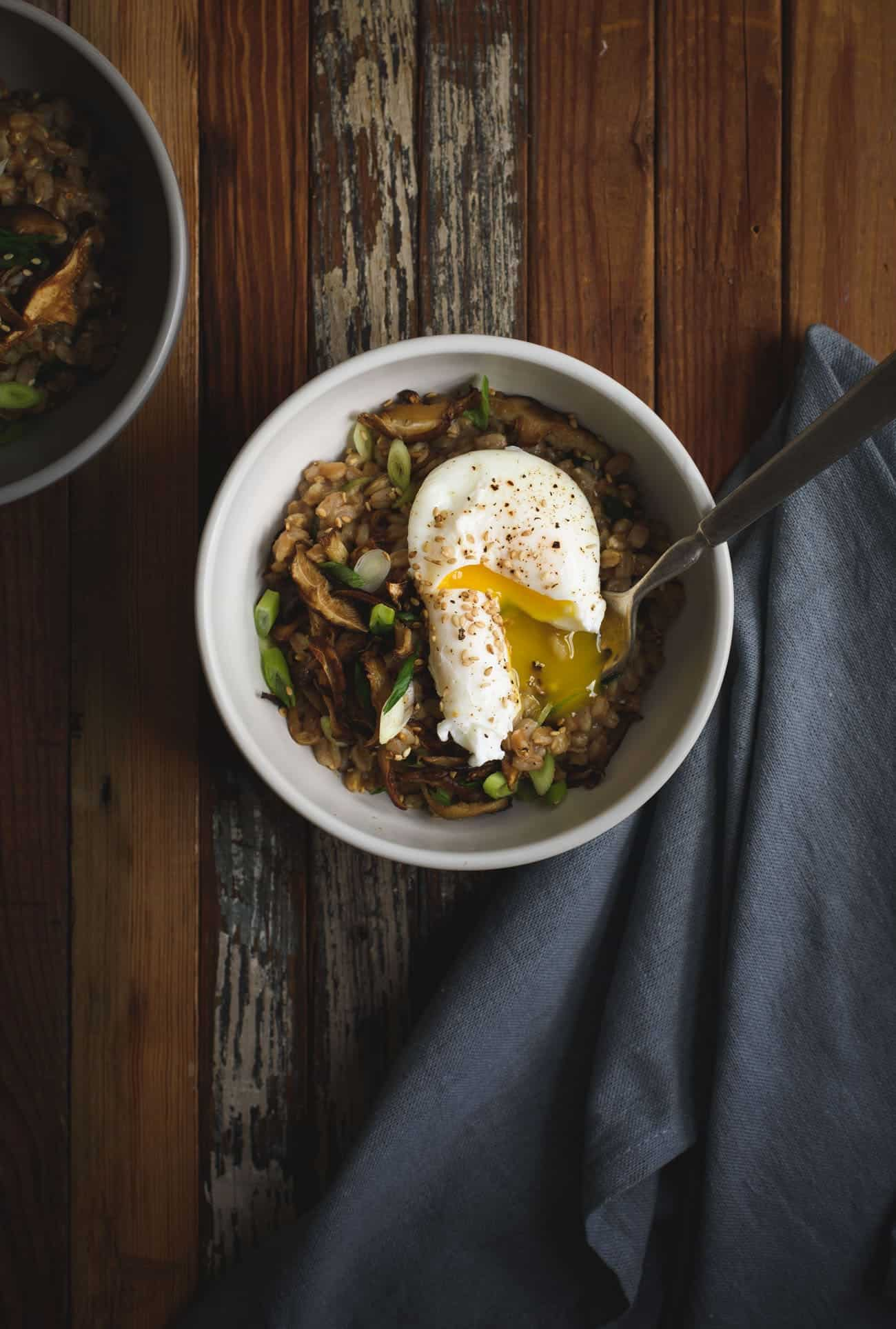 Savory farro porridge with a runny egg in a white bowl on a dark wooden background