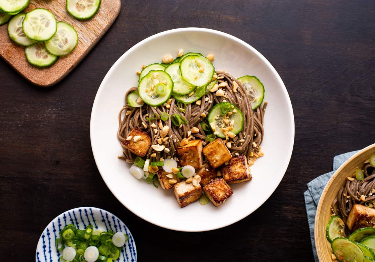 Soba noodle bowl with tofu, cucumbers, and peanuts on a dark wooden table.