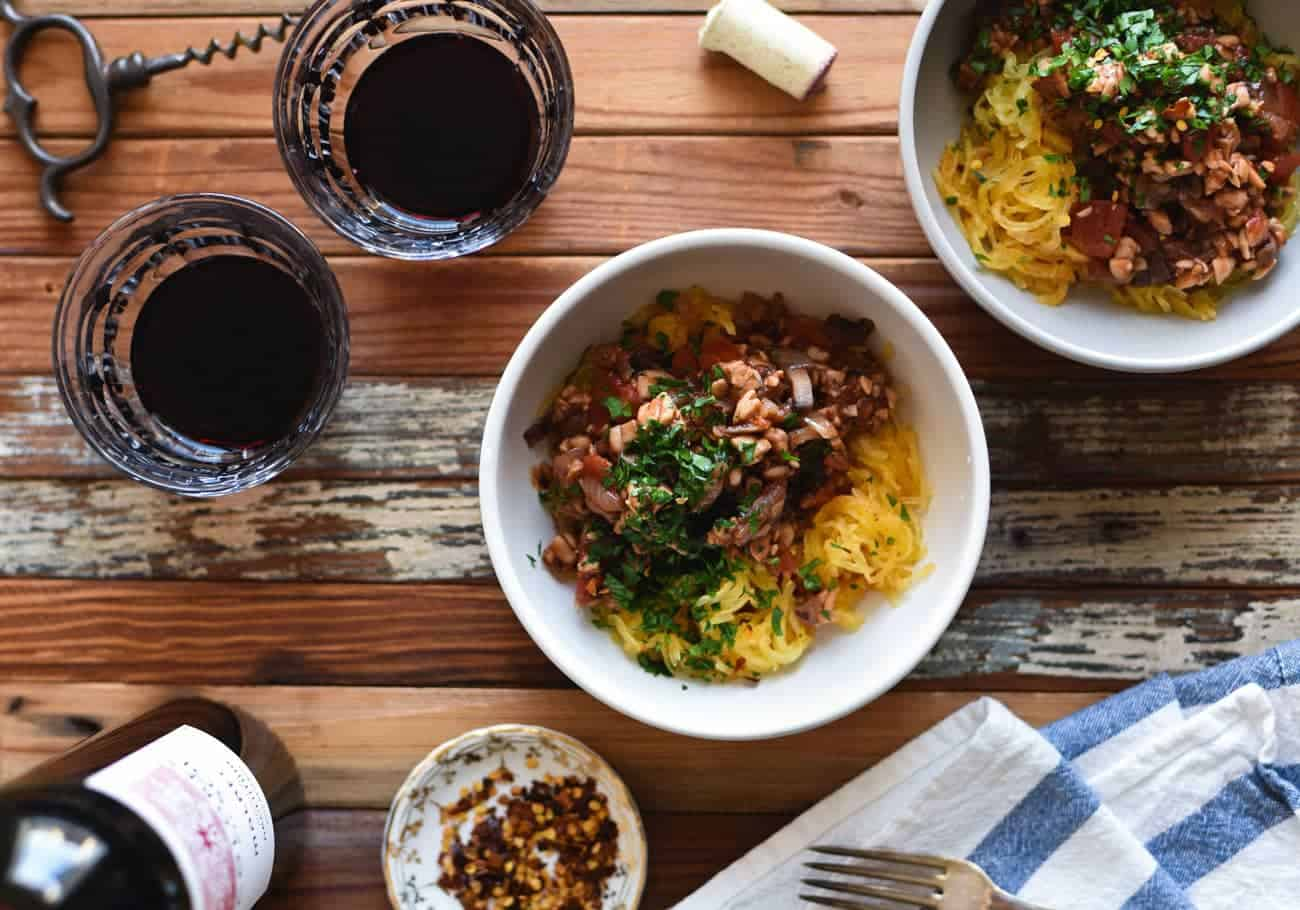 Two bowls with Tempeh Bolognese with Roasted Spaghetti Squash next to glasses of red wine