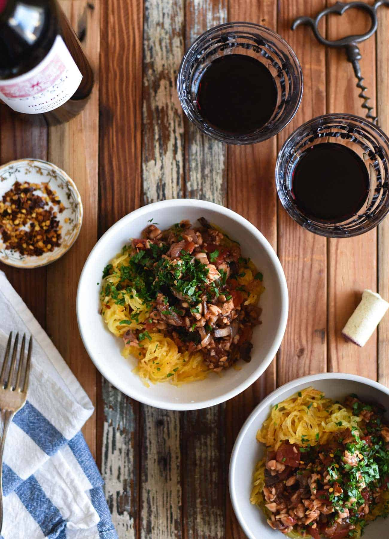 Two bowls of Tempeh Bolognese with Roasted Spaghetti Squash next to glasses of red wine