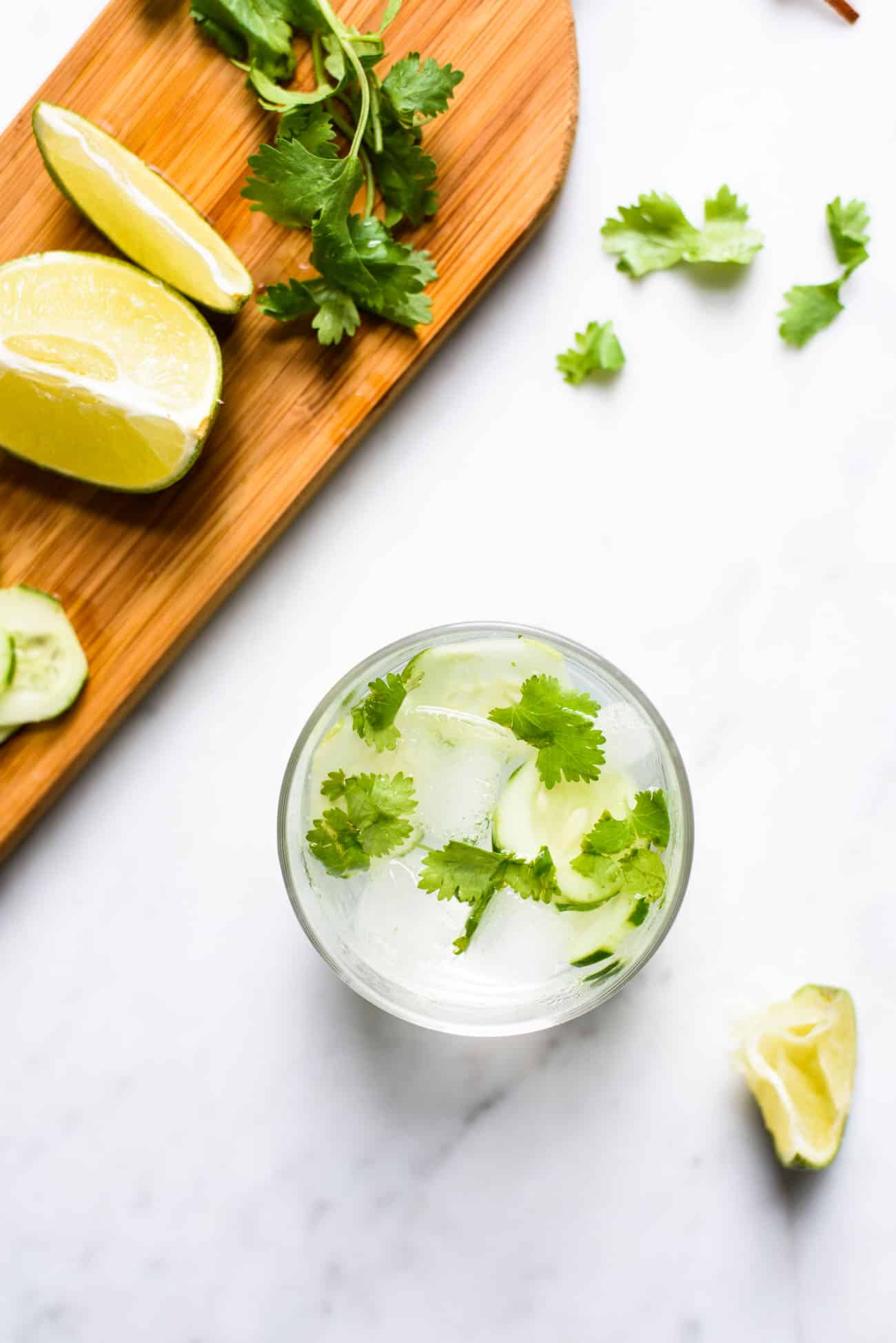 Cilantro cucumber gin and tonic on a marble table next to a wooden cutting board