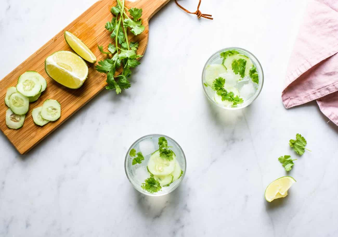 Two cilantro cucumber gin and tonics on a marble table