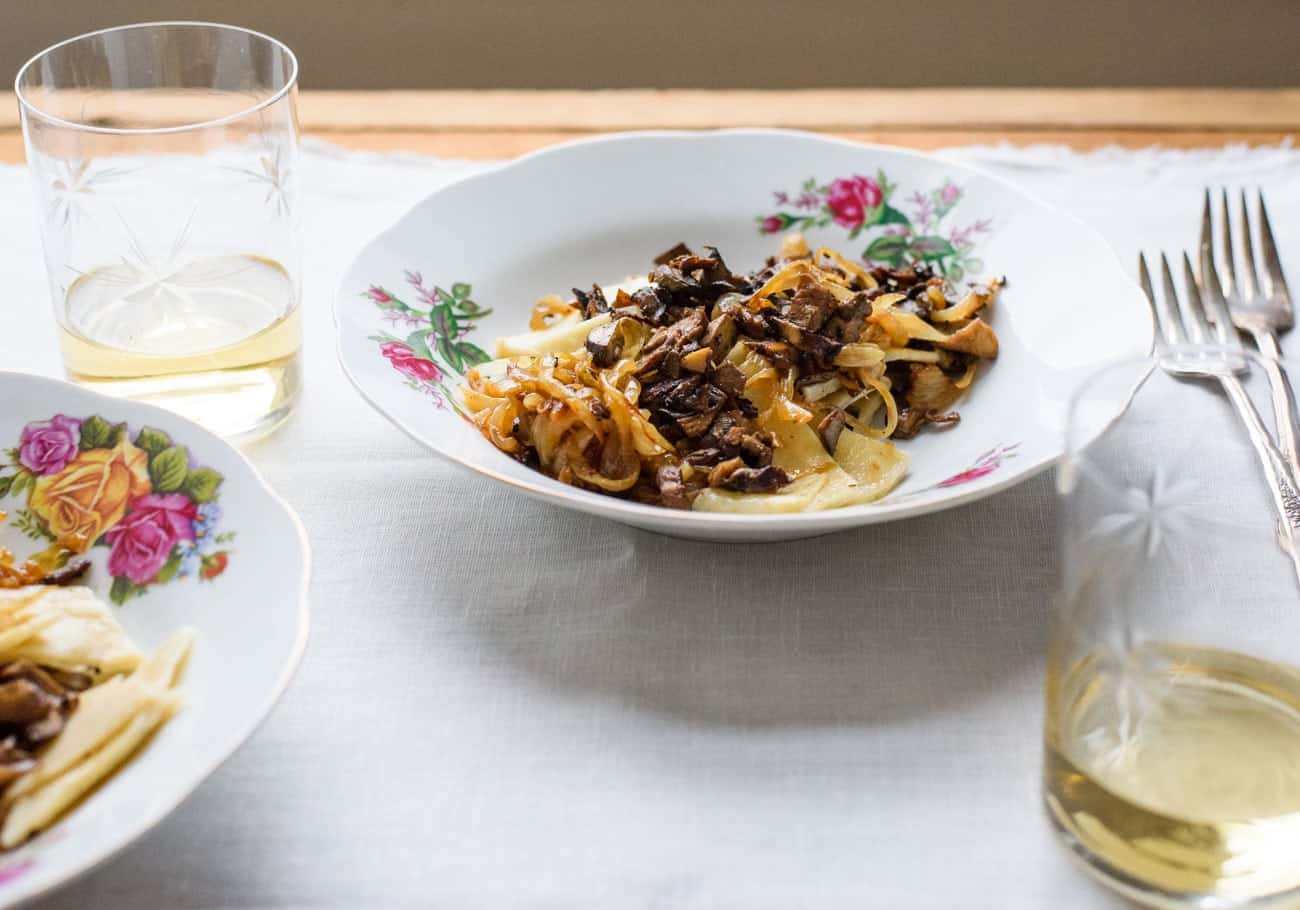 Azerbaijani cuisine: Khingal (handmade noodles) | Noodles with mushrooms and caramelized onions on a floral plate on a white tablecloth