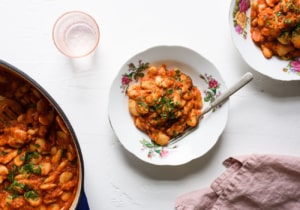 Two bowls of tomato braised beans next to a Dutch oven and pink linen napkin