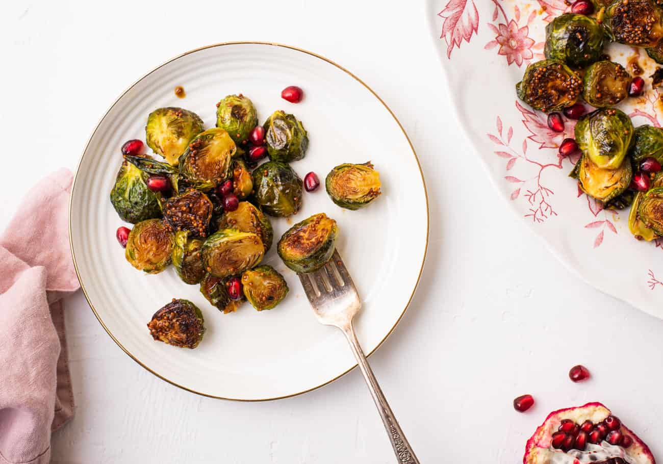 Charred Brussels sprouts in a balsamic glaze with pomegranate on a small white plate