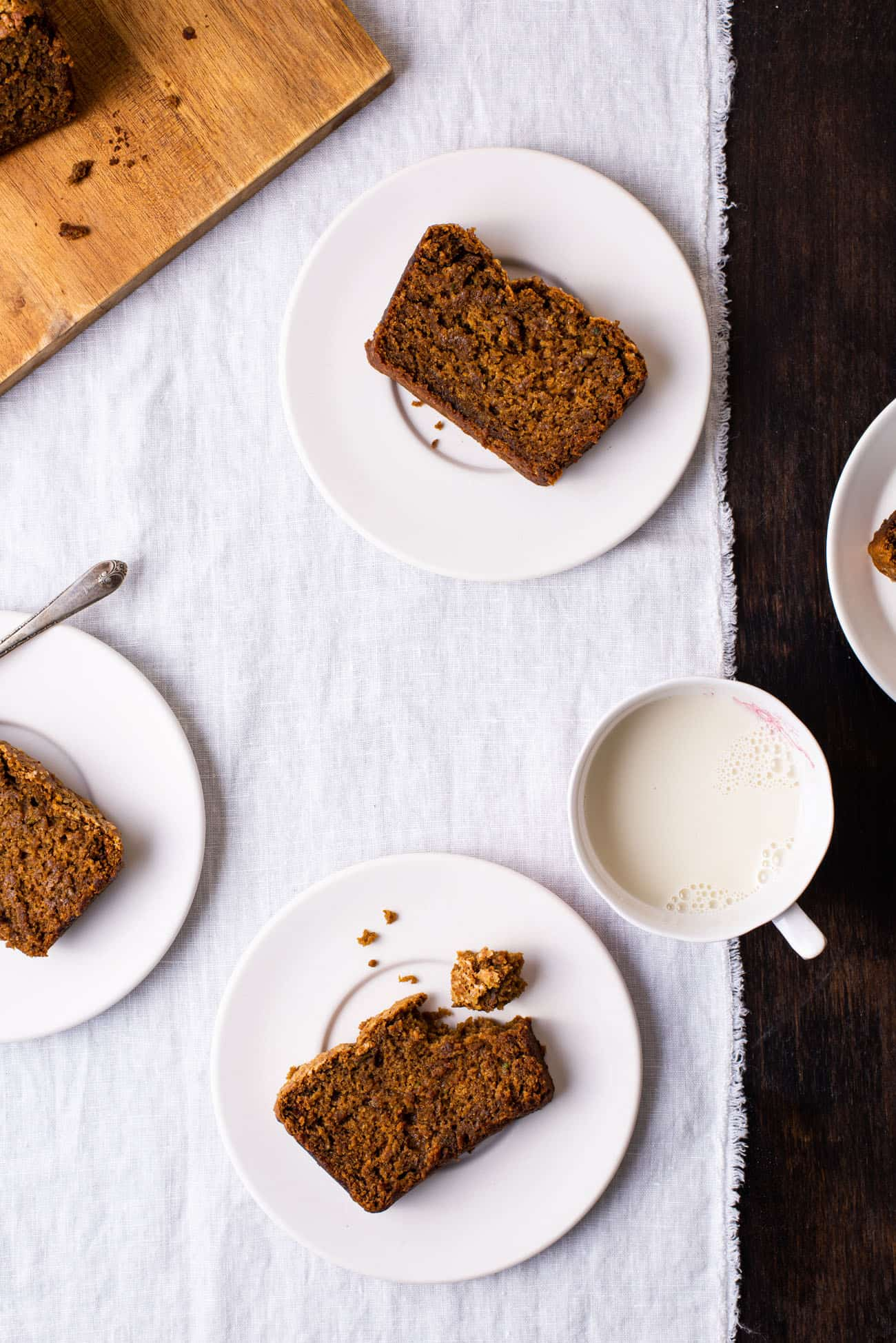 Slices of vegan gingerbread loaf cake on white plates on a white tablecloth next to a cup of milk