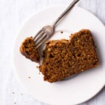 A close-up photo of a slice of vegan gingerbread loaf cake on a white plate