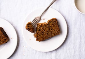 Slices of gingerbread loaf cake on white plates on a white tablecloth