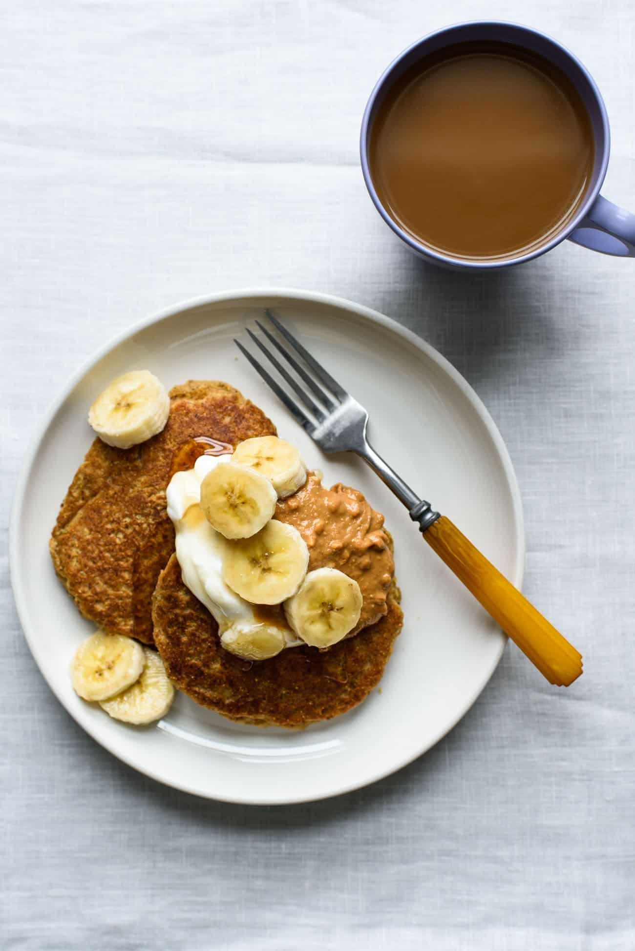 Vegan cornmeal pancakes topped with yogurt, bananas, and peanut butter on a white plate next to a cup of coffee