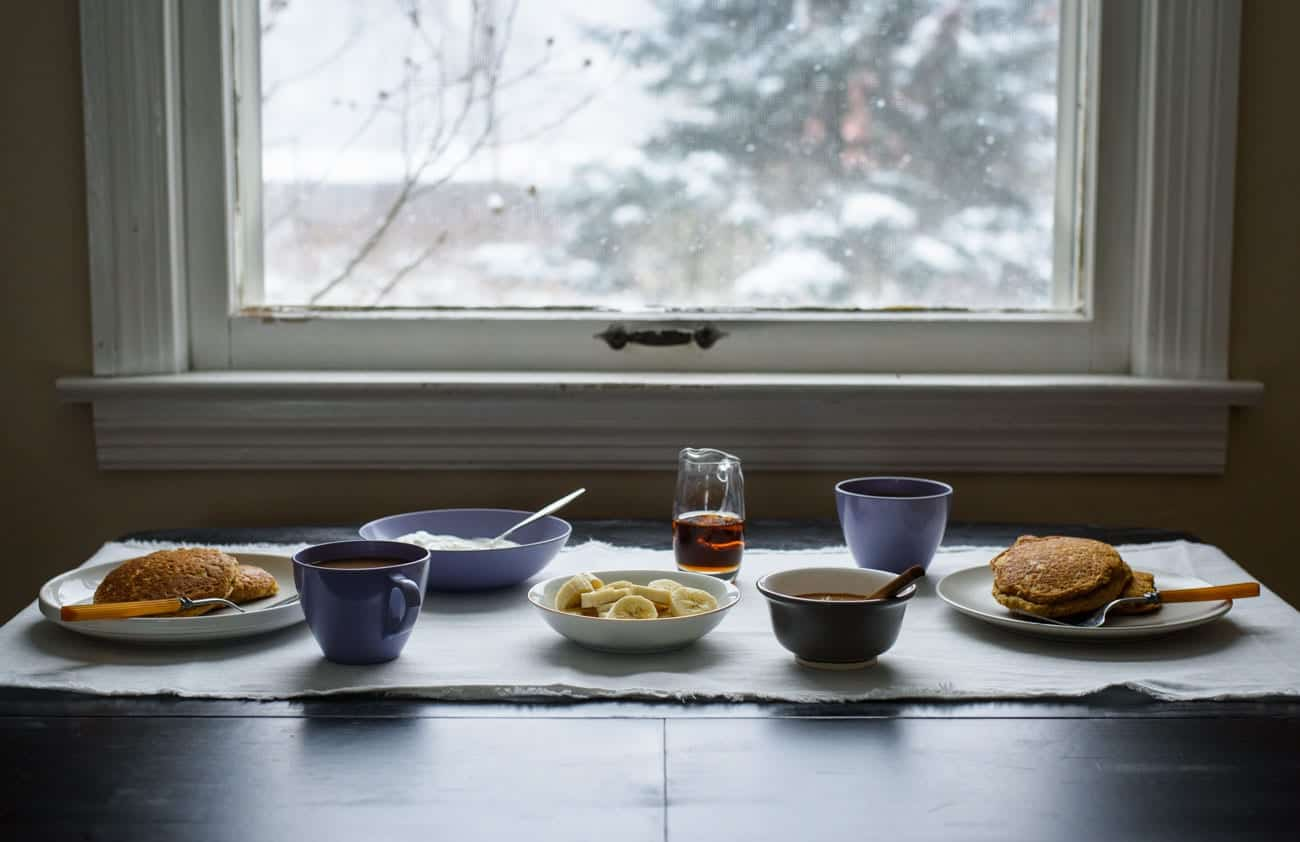 Breakfast table setting with pancakes, syrup, and coffee next to a window with snow outside
