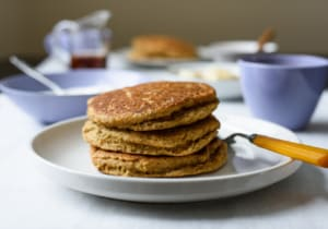 Stack of vegan cornmeal pancakes on a white plate