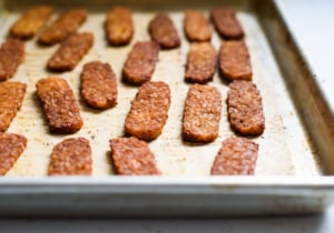 Three-quarter angle photo of tempeh bacon on a baking sheet