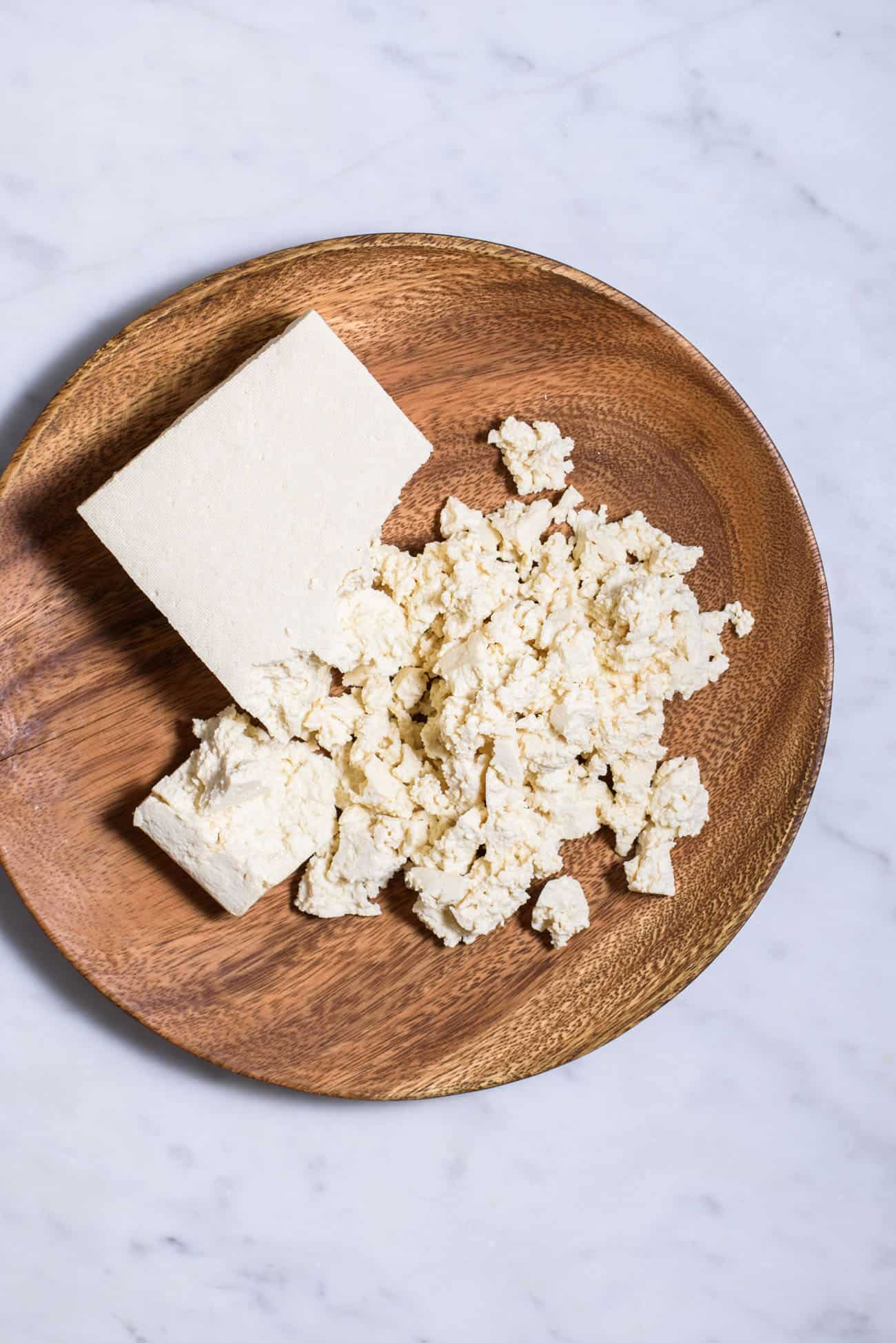Crumbled tofu on a wooden plate