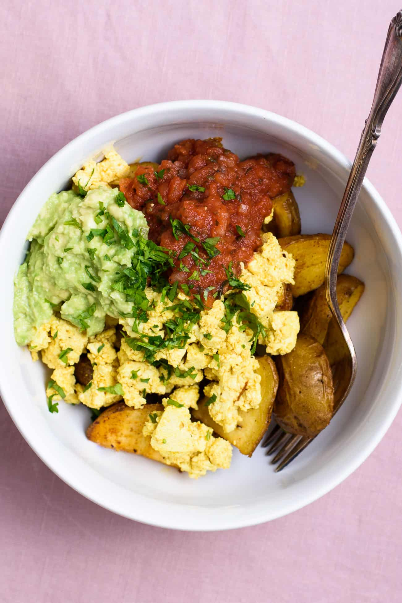 Vegan breakfast bowl with a Mexican tofu scramble, crispy roasted potatoes, guacamole, and salsa