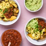 Two vegan breakfast bowls with a Mexican tofu scramble, crispy roasted potatoes, guacamole, and salsa on a pink tablecloth