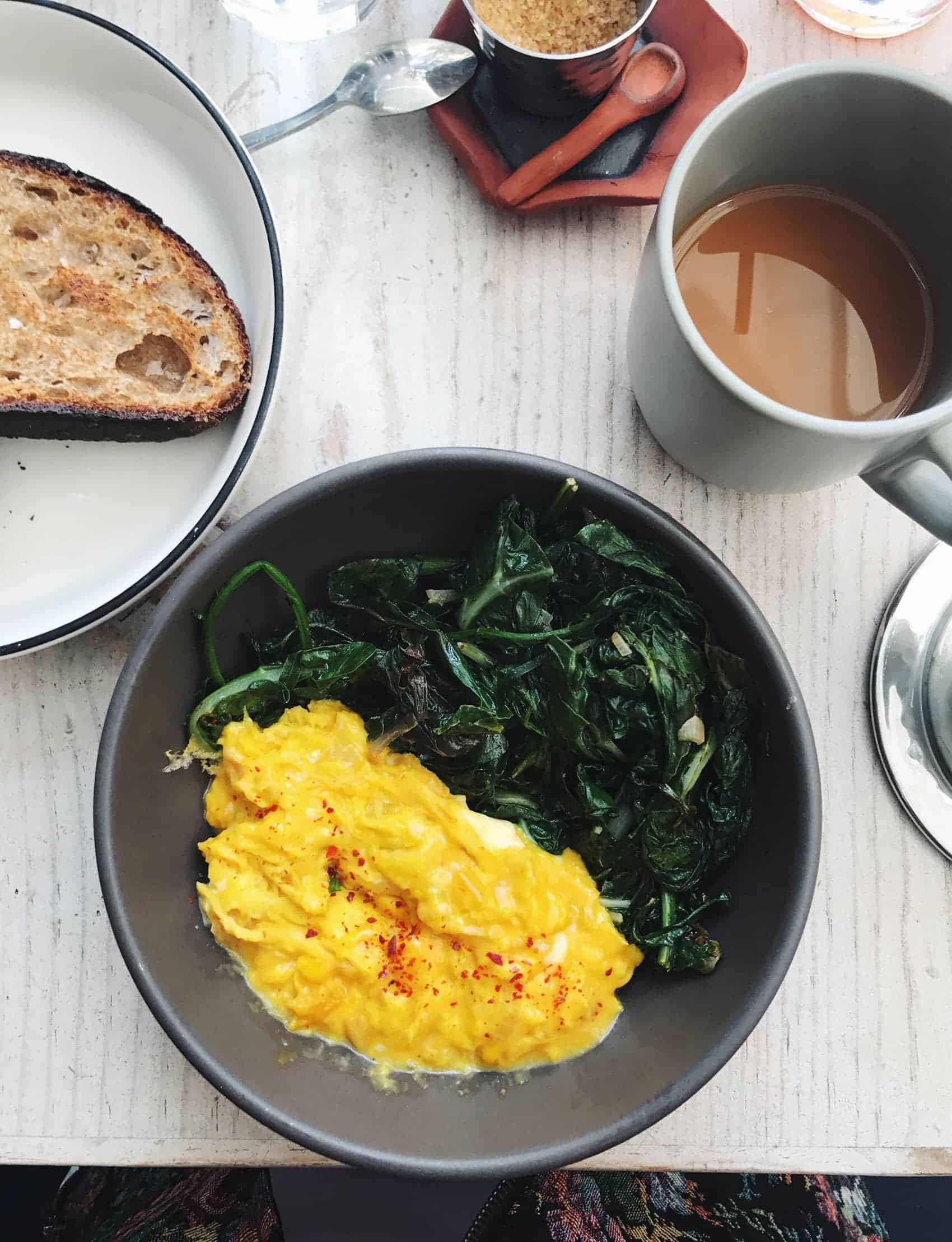 Soft-scrambled eggs in a bowl with sauteed greens | Botanica restaurant in Los Angeles