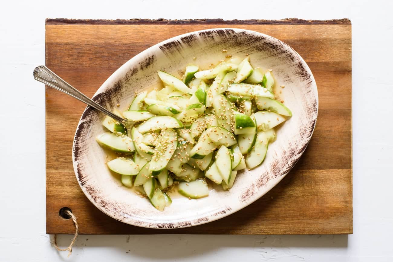 Asian cucumber salad on an oval platter on a wooden board