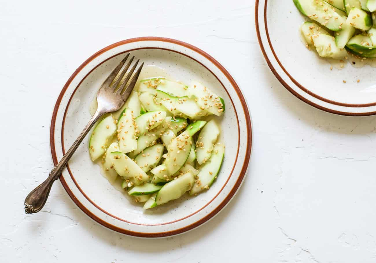 Asian cucumber salad on two plates on a while table