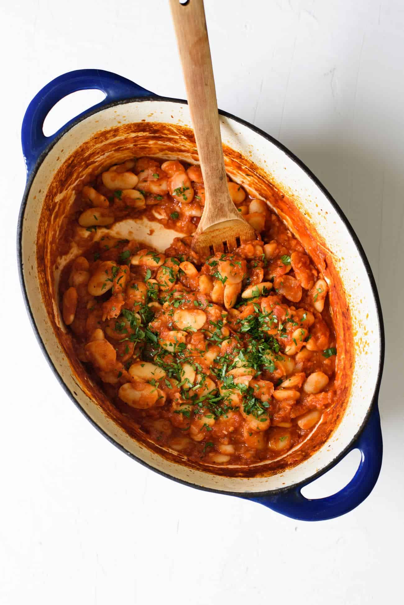 Tomato braised beans in a blue Dutch oven