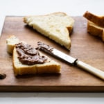 Homemade chocolate hazelnut spread (DIY Nutella) on toast on a wooden cutting board