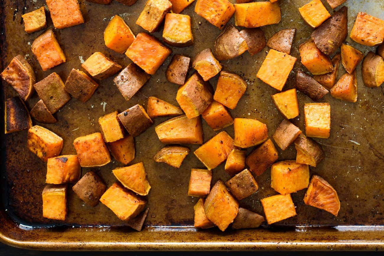 Roasted cubed sweet potatoes on a baking sheet
